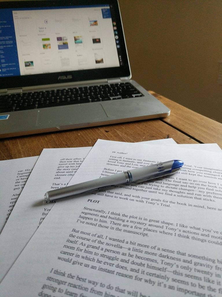 Picture of a developmental editing letter and a laptop, with pen.